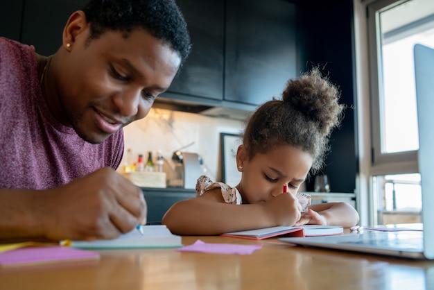 Отец помогает и поддерживает свою дочь в онлайн-школе, оставаясь дома.