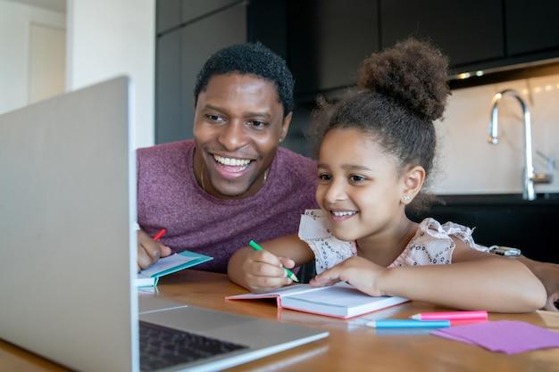 Отец помогает и поддерживает свою дочь в онлайн-школе, оставаясь дома