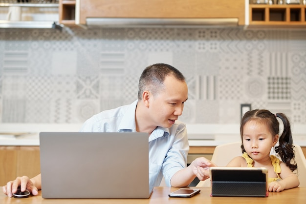 Father helping daughter to find cartoon to watch online on tablet computer when they are sitting at kitchn table