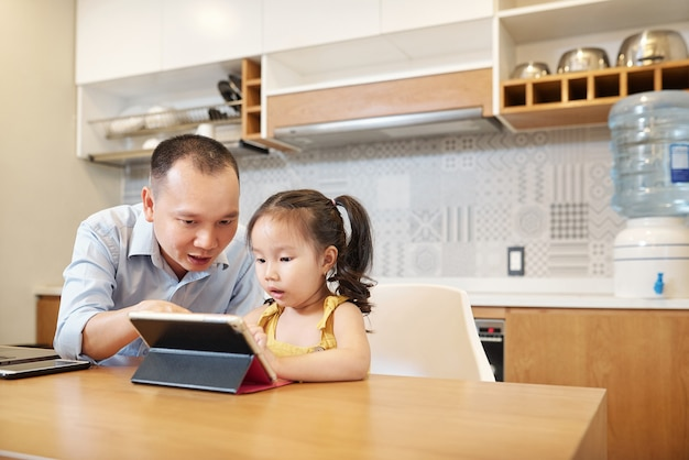 Father helping daughter to solve task in online educational application