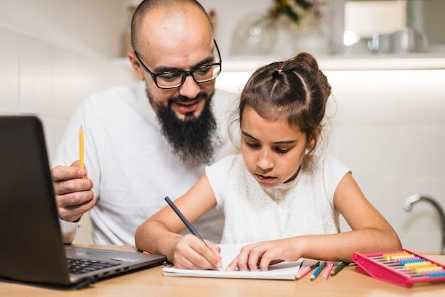 Отец помогает дочери с домашним заданием с помощью цифровой записной книжки.