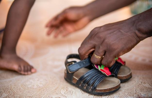 父親は女の赤ちゃんが靴を履くのを手伝っています