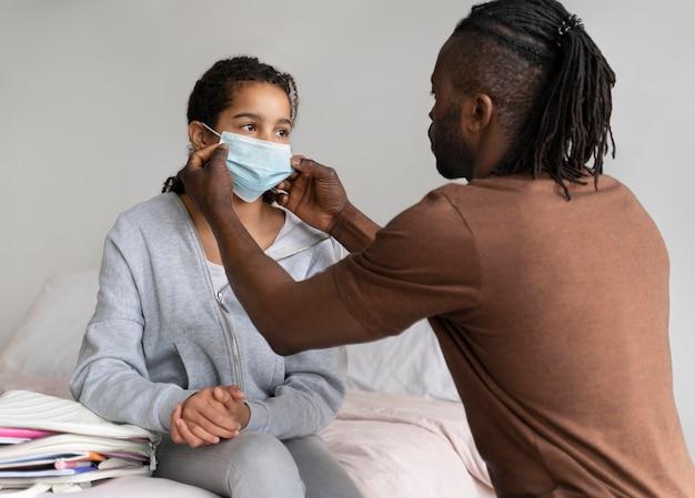 그의 딸이 그녀의 의료 마스크를 넣어 돕는 아버지