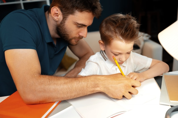 Father helping his little son with school homework