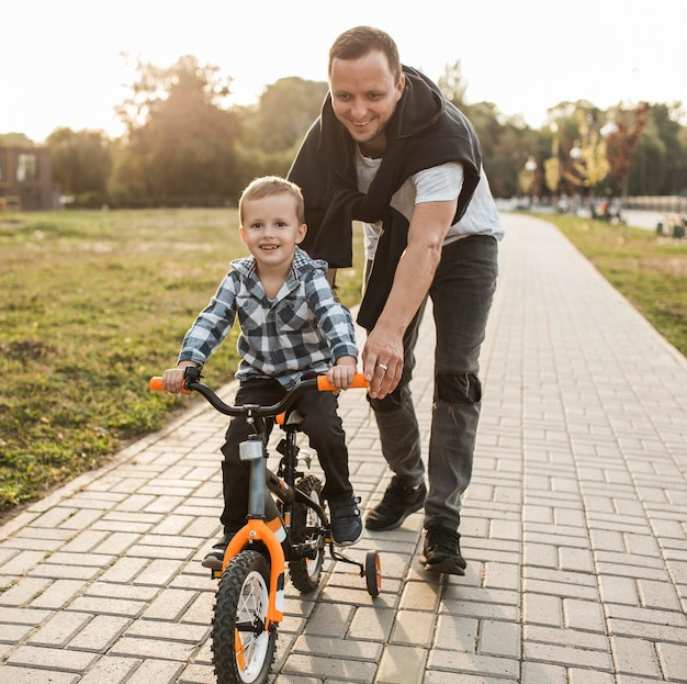 Padre che aiuta suo figlio in sella alla bicicletta