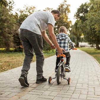 Отец помогает своему сыну ехать на велосипеде сзади выстрел