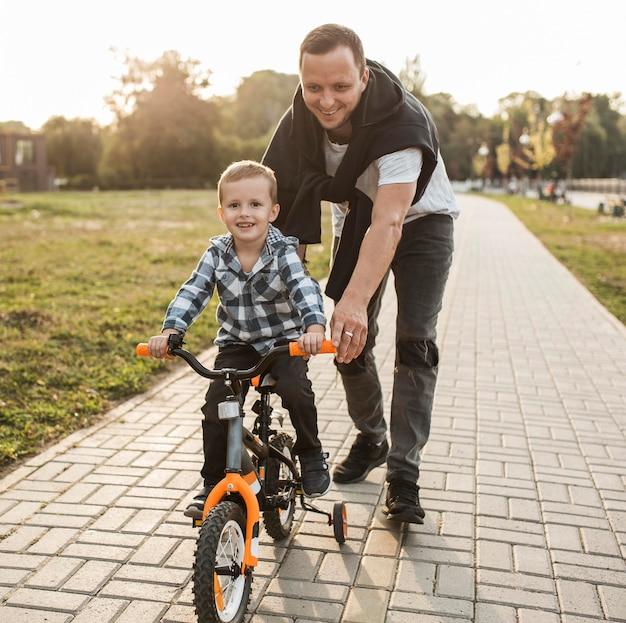 Отец помогает своему сыну на велосипеде