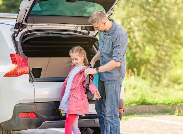 車のトランクの近くの放課後、父親が娘のバックパックを脱ぐのを手伝う