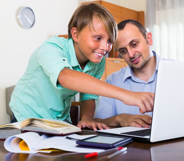 Father helping teenage son with homework