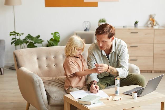 部屋のテーブルのソファに座って宿題をしている幼い息子を手伝っている父