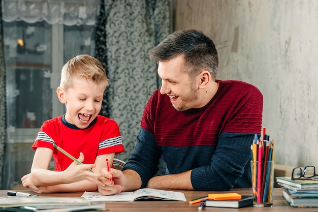 The father helps his son to do homework for the school.