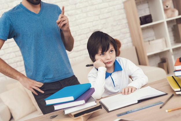 Father helps his son to do homework.