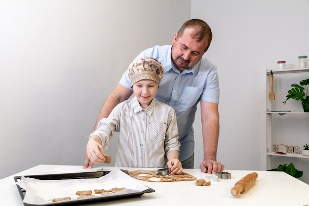 Father helps his son make cookies for the holiday