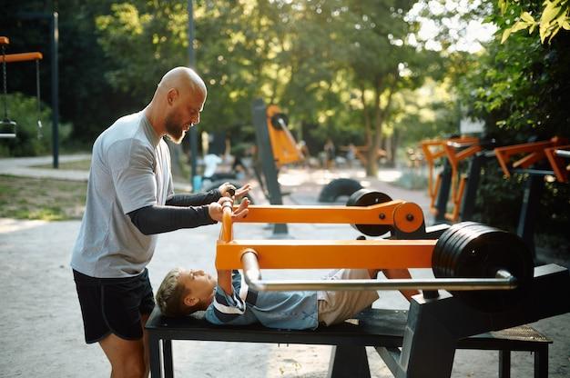父は息子の運動器具や屋外の遊び場でのスポーツトレーニングを手伝っています。家族は夏の公園で健康的なライフスタイル、フィットネストレーニングをリードしています