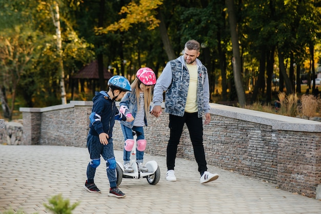 A father helps and teaches his young children to ride a segway in the park during sunset