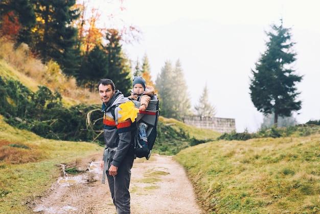 Отец, походы с ребенком в рюкзаке для переноски на природе в осеннем лесу семья в горах