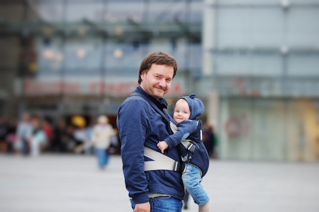Father and his baby boy in a baby carrier at the big city