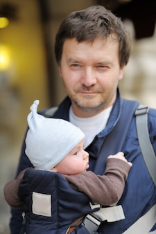 Father and his baby boy in a baby carrier, outdoors portrait