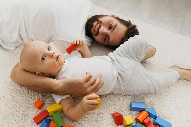 Padre e il suo bambino sul pavimento a casa