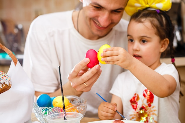 Father and his daughter are painting eggs.