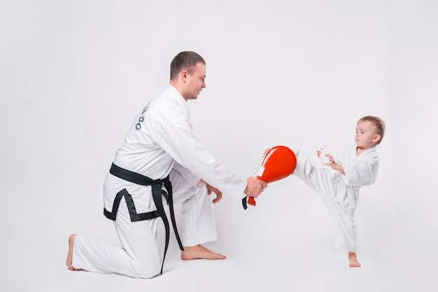 Father and his little boy practicing taekwondo on white