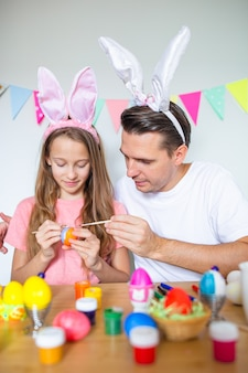 Father and his little daughter painting eggs happy family preparing for easter