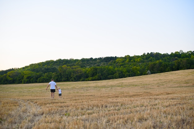Father and his little son are walking along a mowed wheat field.