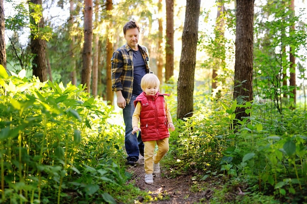 Father and his little son during the hiking activities in forest at sunset