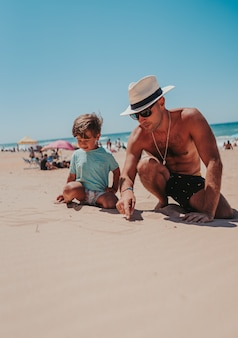 Father and his son happily playing in the sandy beach