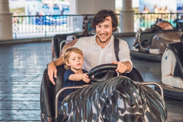 Father and his son having a ride in the bumper car at the amusement park.