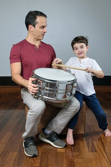 Father and his son with a drum and sticks