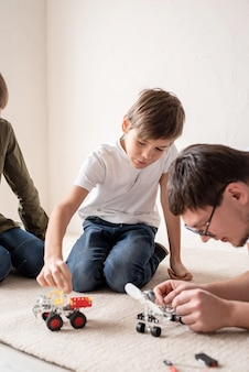 Father and his sons spending time together, having fun constructing robot cars at home sitting on the rug
