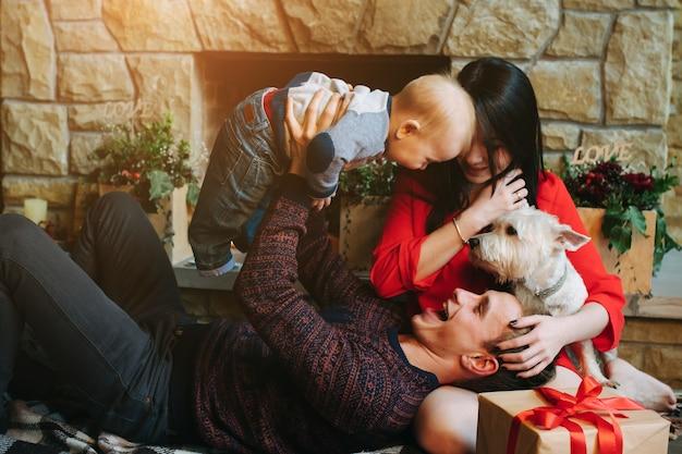 Отец держит ребенка в то время как его жена смотрит на них