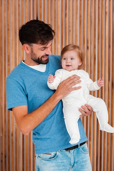 Father holding baby with wooden background