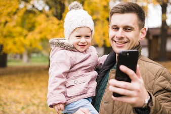 Father holding daughter smiling and doing selfie together