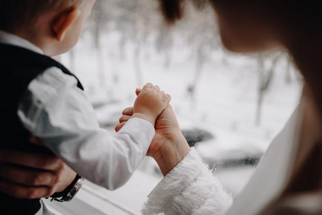 父はスタジオの黒の背景に座っている彼の息子の手を握って。男の赤ちゃんと成人男性のクローズアップの手。