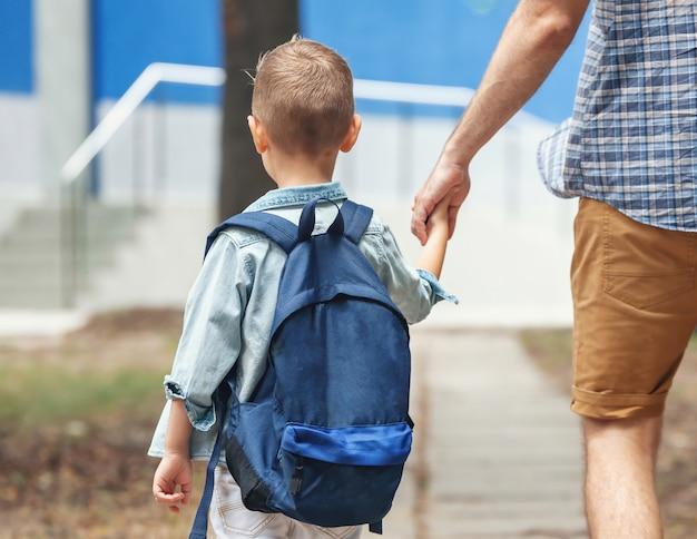 Отец, держащий руку маленького сына с рюкзаком на открытом воздухе. обратно в школу. первый день осени.