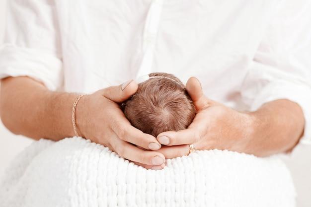Отец держит в руках голову своей новорожденной дочери. ребенок на руках у папы.