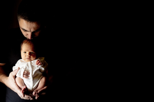 Father holding his 15 days old son in his hand on black.