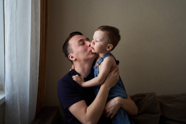 Father holding in his arms his little son and kissing him at home
