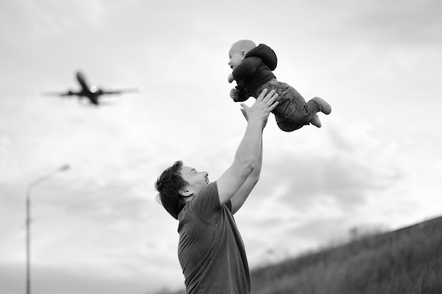 Father holding his baby and airplane on the sky