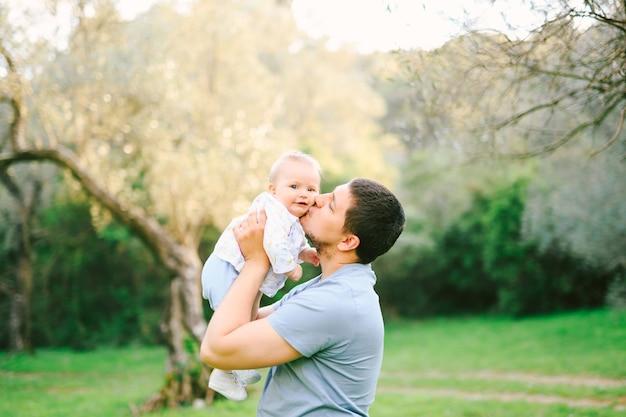 그의 팔에 그의 딸을 안고 그녀를 뺨에 키스하는 아버지