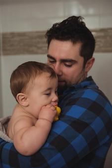 赤ちゃんをバスルームに抱っこしている父