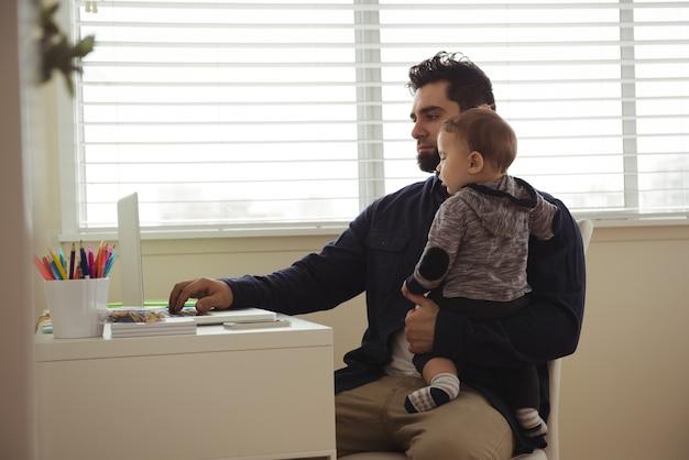 Отец держит своего ребенка во время использования ноутбука за столом