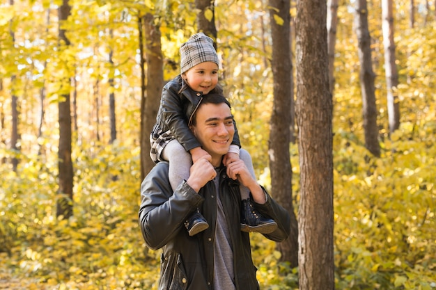 Father holding his daughter in autumn park