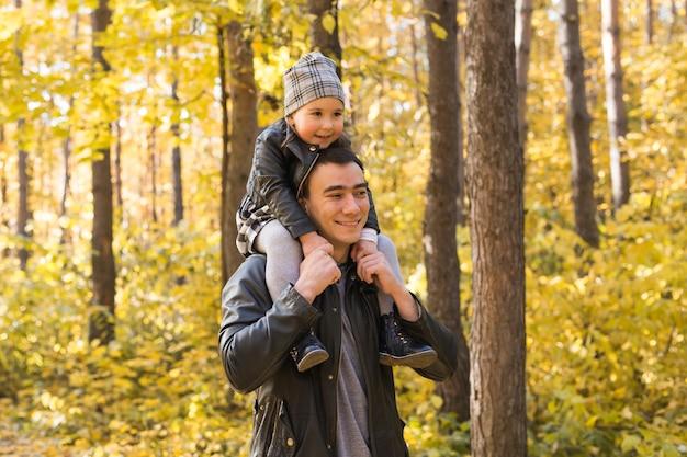 秋の公園で娘を抱いて父