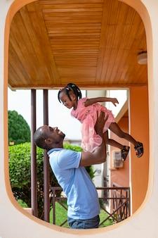 彼の小さな黒い女の子を保持している父