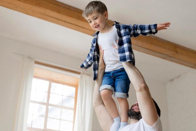 Отец держит своего сына в воздухе в помещении