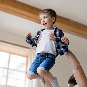 Отец держит своего сына в воздухе