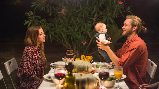 Father holding little baby near lady on family dinner